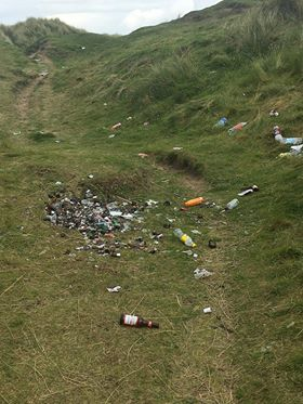 Cans and broken bottles strewn close to Benone Strand boardwalk.