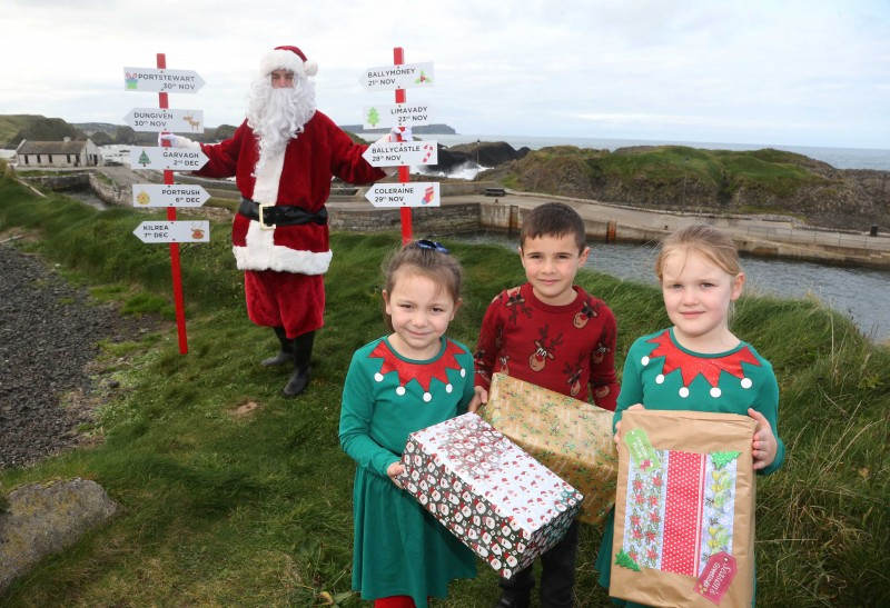 Santa Claus pictured at Ballintoy Harbour with Daisy, Charlie and Hannah from Dunseverick Primary School, as he prepares to take part in Causeway Coast and Glens Borough Council's upcoming Christmas lights switch-on events in towns and villages across the area.
