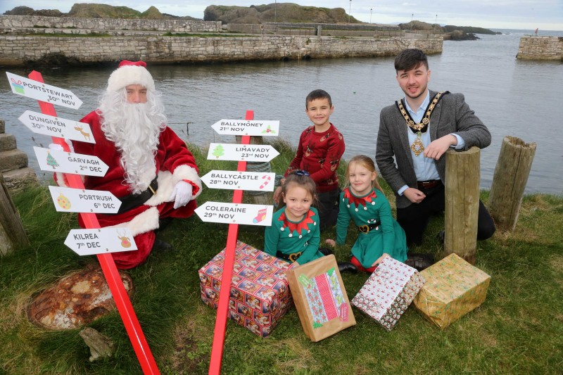 The Mayor of Causeway Coast and Glens Borough Council Councillor Sean Bateson pictured with Santa Claus at Ballintoy Harbour along with Dunseverick Primary School pupils Daisy, Charlie and Hannah ahead of Causeway Coast and Glens Borough Council's upcoming Christmas lights switch-on events in towns and villages across the area.