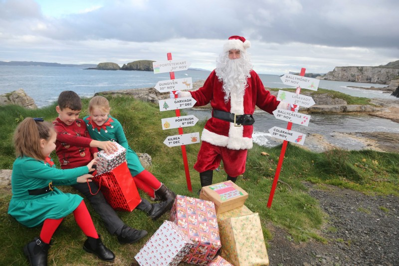 Daisy, Charlie and Hannah, Primary 4 pupils at Dunseverick Primary School, pictured with Santa Claus at Ballintoy Harbour as he prepares to take part in Causeway Coast and Glens Borough Council's upcoming Christmas lights switch-on events in towns and villages across the area.