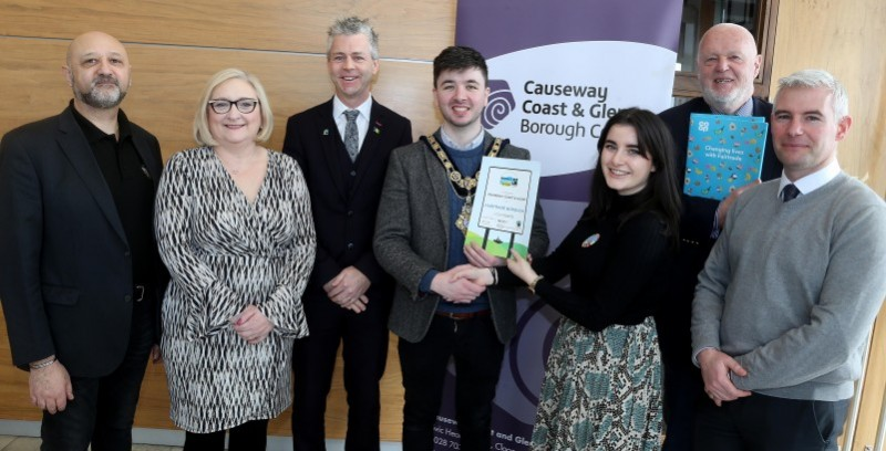 The Mayor of Causeway Coast and Glens Borough Council Councillor Sean Bateson receives the Fairtrade Borough award from Lucy Geraty, Fairtrade Ireland Project and Support Officer, alongside (l-r) Nick Lestas (Fairtrade Steering Group), Councillor Brenda Chivers, Consul General Dr Christopher Stange, Secretariat of the All Party Group on Fairtrade, Chris McCaughan (Fairtrade Steering Group) and Aidan McPeake, Causeway Coast and Glens Borough Council's Director of Environmental Services and Secretariat of Steering Group.