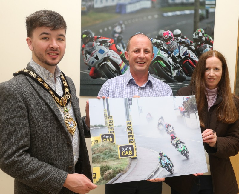 The Mayor of the Causeway Coast and Glens Borough Council, Councillor Sean Bateson pictured with Fergus Mackay, Event Operations Manager of the NW200 and Jane Blakely, winner in the Open Category in this year's 'Capture the Moment' International NW 200 photography competition.