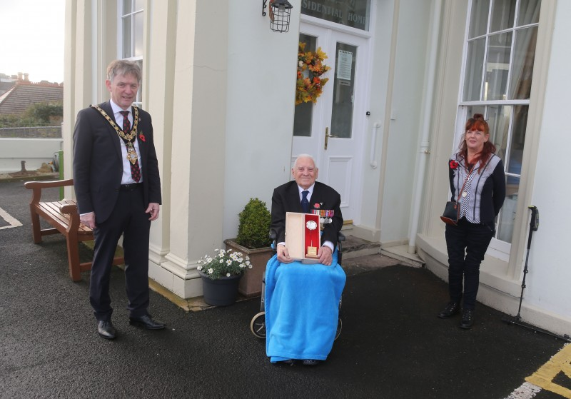 Royal Air Force Flight Lieutenant Geoff Bainbridge pictured with his silver Poppy of Remembrance, alongside his daughter Lorna Gough and Mayor of Causeway Coast and Glens Borough Council Alderman Mark Fielding.
