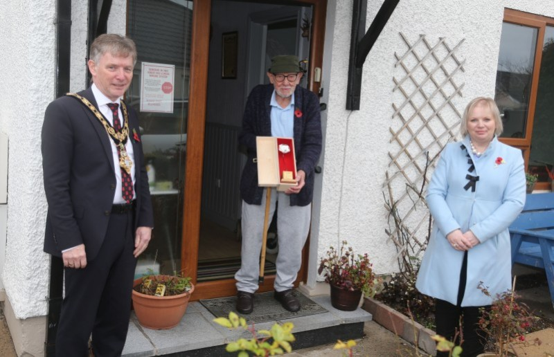 Royal Navy Able Seaman Thomas Clarence receives his silver Poppy of Remembrance from the Mayor of Causeway Coast and Glens Borough Council Alderman Mark Fielding and Veterans' Champion Councillor Michelle Knight McQuillan.