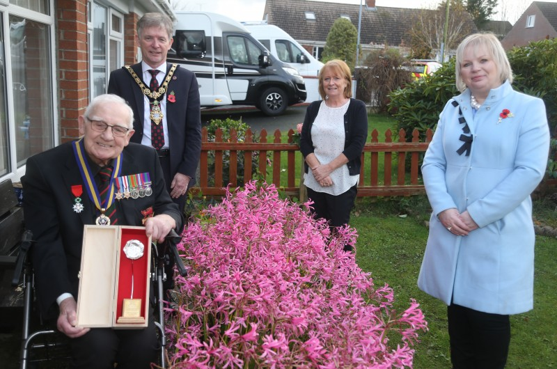 Rifleman Andrew Nicholl, Royal Ulster Rifles, displays his silver Poppy of Remembrance with his niece Andree Tweed alongside the Mayor of Causeway Coast and Glens Borough Council Alderman Mark Fielding and Veterans' Champion Councillor Michelle Knight McQuillan.