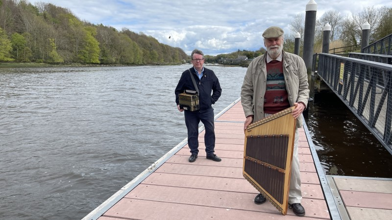 Musicians Dick Glasgow and Ciaran Kelly, who will perform as part of the virtual Rhythm of the Bann event pictured alongside the River Bann in Coleraine.