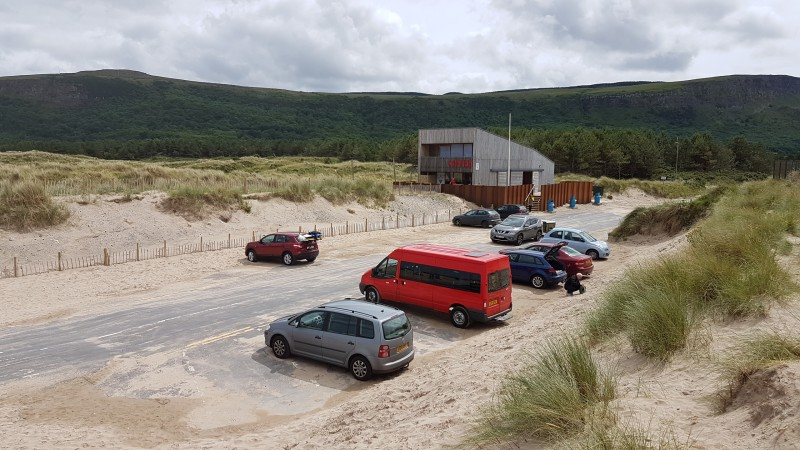 Car parking at beach entrance, with The Ark in background