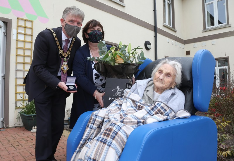 Sarah Wilson receives her NI 100 commemorative coin to mark her 100th birthday from the Mayor of Causeway Coast and Glens Borough Council Alderman Mark Fielding and Mayoress Mrs Phyllis Fielding.