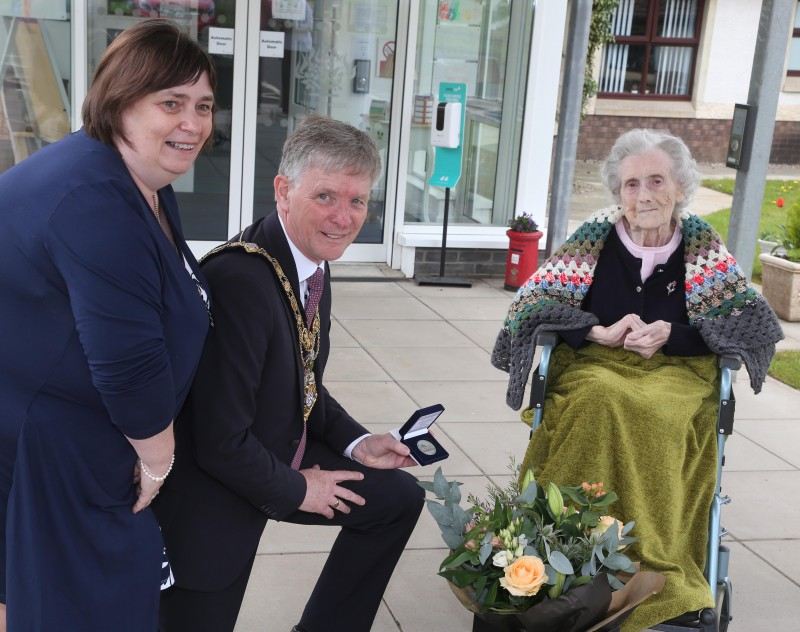 Christina McMullan, who celebrated her 100th birthday on January 23rd, receives her NI 100 commemorative coin from the Mayor of Causeway Coast and Glens Borough Council Alderman Mark Fielding and Mayoress Mrs Phyllis Fielding.