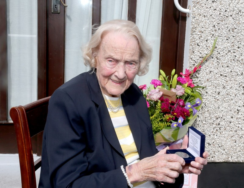 100-year-old Isabelle Claypole displays her commemorative centenary coin received from the Mayor of Causeway Coast and Glens Borough Council Alderman Mark Fielding.