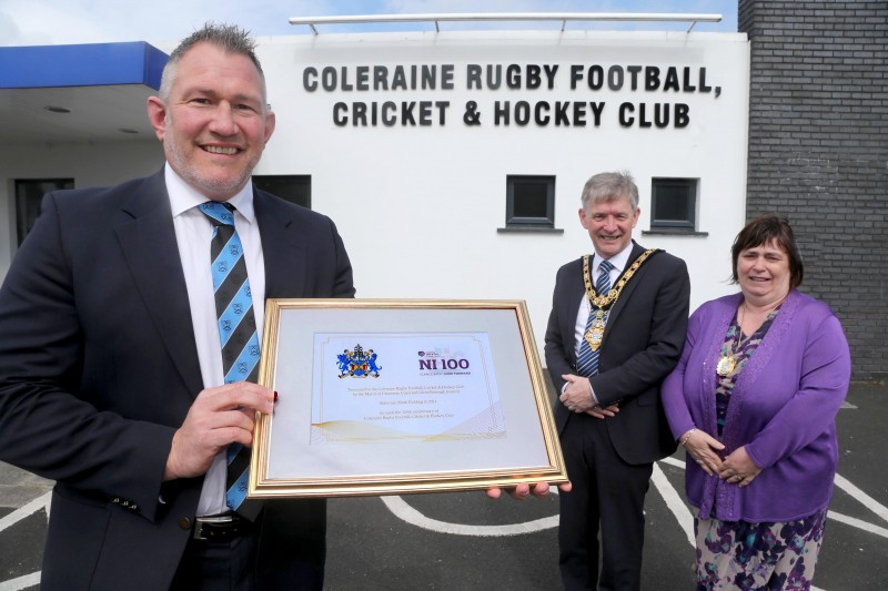 The Mayor of Causeway Coast and Glens Borough Council Alderman Mark Fielding and Mayoress Mrs Phyliss Fielding present a framed certificate to Andrew Hutchinson, President of Coleraine Rugby Football, Cricket and Hockey Club, to mark the club's centenary.