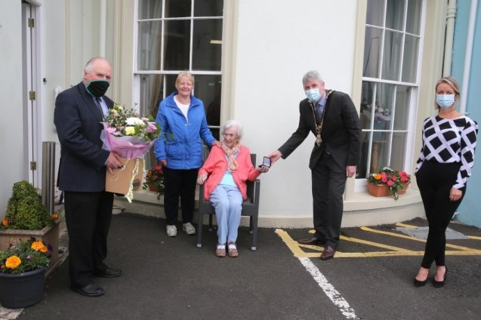 Centenarian receives commemorative coin from Mayor of Causeway Coast and Glens Borough Council